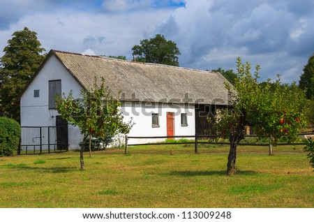 Farm house and apple orchard in rural landscape of Poland