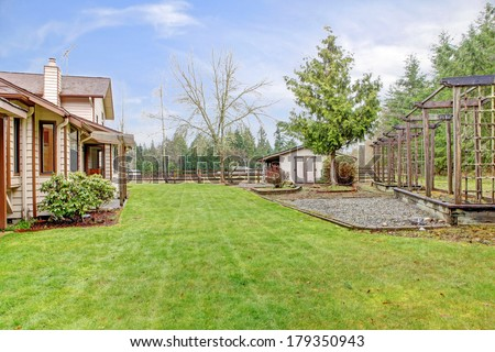 Farm house backyard with a lawn, trees and wooden grids. View of the fenced horse barn