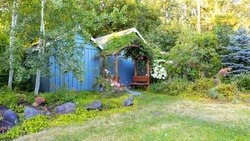 Farm house backyard with wood sheds, attached garden house,  flourishing flower bed