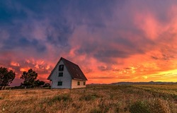 Farm house in a field at sunset. Sunset farm house view. Sunset farm. Farm house at sunset