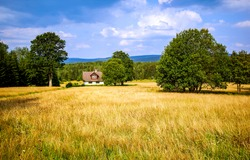 Farm house in the middle of a field. Summer farmland landscape. Agriculture field at farm house