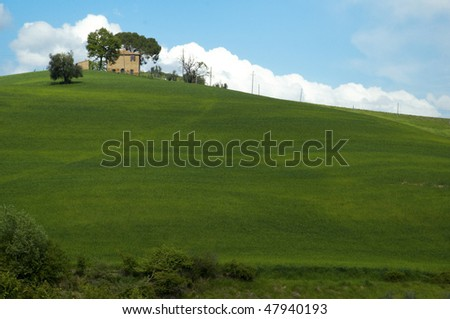 Farm house villa in Tuscany, Italy, on green field and hill in spring.