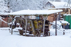 Farm in the forest in winter. Old houses and sheds by the lake. Old agricultural machinery. Yard in the village