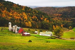 Farm in valley of hills during Fall with autumn colors showing on a dreary evening low contrast from a high angle above on the hill