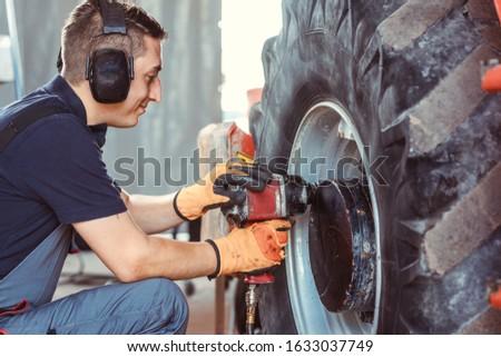 Farm machine mechanic working on wheel with power tool Stockfoto ©