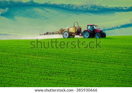 Farm machinery spraying insecticide to the green field, agricultural natural seasonal spring background