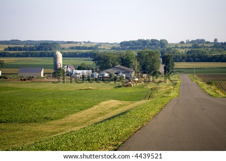 Farm shown along a wide road at dusk