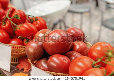 Farm tomatoes in a basket lie in the window of the farmer's market. The latest hybrid varieties of vegetables