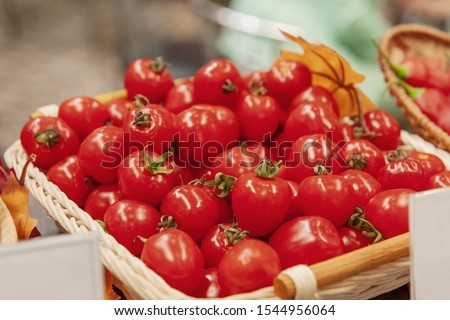 Farm tomatoes in a basket lie in the window of the farmer's market. The latest hybrid varieties of vegetables.