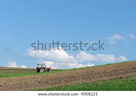 Farm tractor plowing arable field