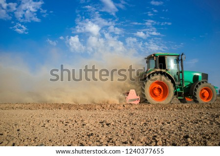 Farm tractor preparing dusty soil affected by drought. Drought and agriculture concept