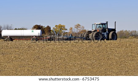 Farm tractor pulling a plow and a nurse tank of anhydrous ammonia fertilizer