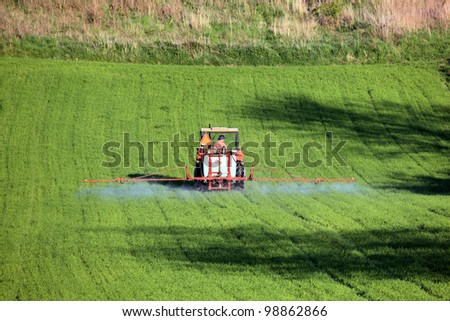 Tractor In Field Planting : Farm tractor spraying field before planting stock photo