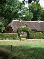 Farm with a hedge of hornbeam in a shape an arch.