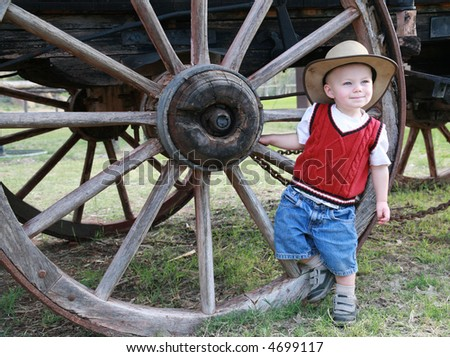 Farmboy:  A baby cowboy hangs out at the wheel of an old farm wagon in a cowboy hat and denim shorts.