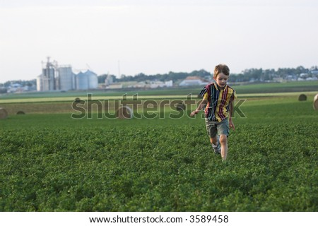 farmboy running through clover field with hay, room in sky for text