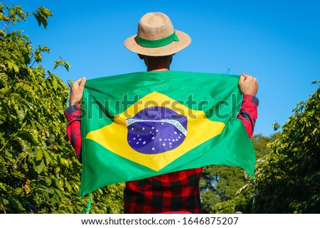 Farmer at coffee plantation holding Brazilian flag.