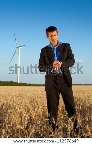 farmer (businessman) standing in wheat field over wind turbines background waiting for the meeting and looking at his watch