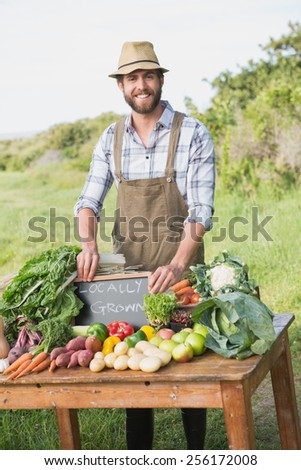 Farmer by his stall at the market on a sunny day
