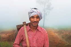 Farmer carrying hoe or sickle on shoulder outdoor in nature.