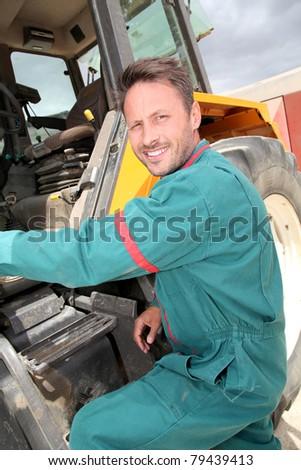 Farmer climbing in tractor