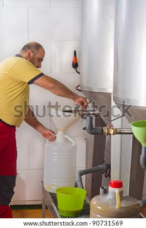 Farmer collecting the freshly pressed oil from his olive crop - stock photo