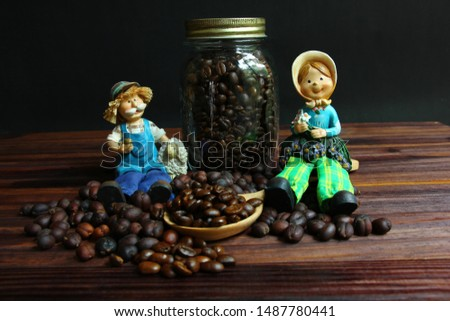 farmer dolls sit on coffee beans.dried coffee beans with roasted coffee beans .coffee beans on wood spoon on brown wood floor .