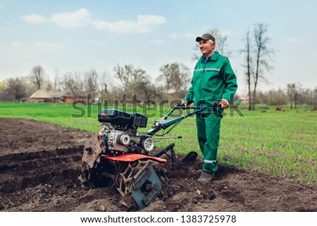 Farmer driving small tractor for soil cultivation and potato planting. Spring preparation #1383725978