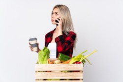 Farmer girl holding a basket full of fresh vegetables over isolated white background holding coffee to take away and a mobile