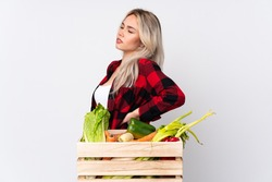 Farmer girl holding a basket full of fresh vegetables over isolated white background suffering from backache for having made an effort