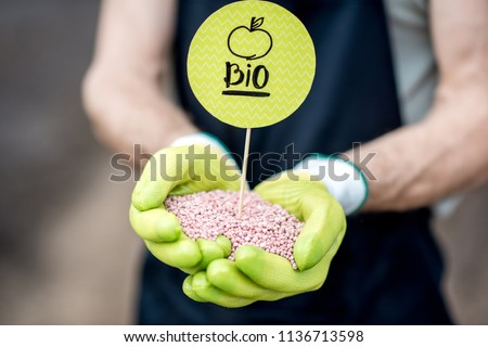 Farmer holding bio fertilizers with green plate, close-up view