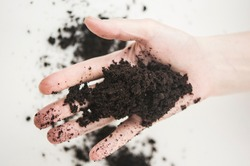 Farmer holding pile of arable soil. Woman agronomist examining quality of fertile agricultural land. Can be used as a fertilizer to accelerate the growth of plants. Soil in hands on white background.
