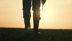 farmer in boots walks the farm close-up at sunset with a tablet in his hands, the concept of work in agriculture, the life of an agronomist in the season of planting cereals, rural land