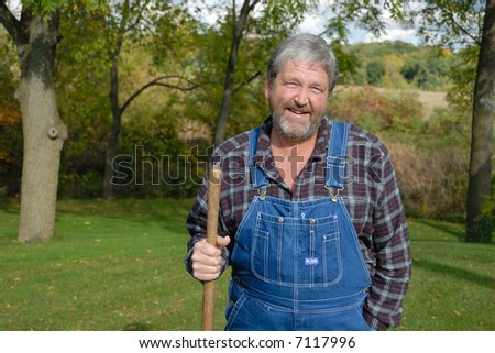 farmer in plaid shirt & dungarees with shovel