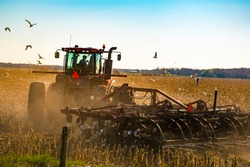 Farmer in red tractor & plow or plough. He is turning, plowing & preparing the soil of his farm. Tillage practices. Cutting furrows before sowing seed or planting. Gulls & Birds flying in crop field.