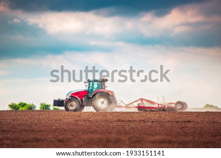 Farmer in tractor preparing land with seedbed cultivator Stockfoto ©