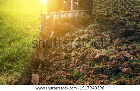 Farmer in tractor preparing land with seedbed cultivator in farmland.