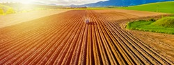 Farmer in tractor preparing land with seedbed cultivator in farmlands. Tractor plows a field. Agricultural work in processing, cultivation of land. Furrows row patter. aerial photo