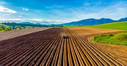 Farmer in tractor preparing land with seedbed cultivator in farmlands. Tractor plows a field. Agricultural work in processing, cultivation of land. Furrows row patter.aerial photo