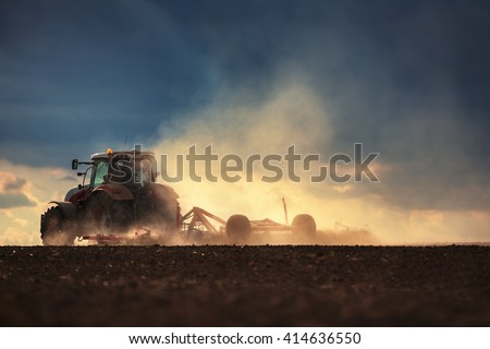 Farmer in tractor preparing land with seedbed cultivator, sunset shot