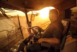 Farmer inside a combine during harvest at sunset