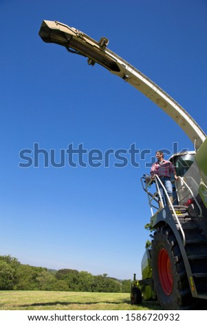 Farmer looking at harvested field whilst standing on forage harvester steps