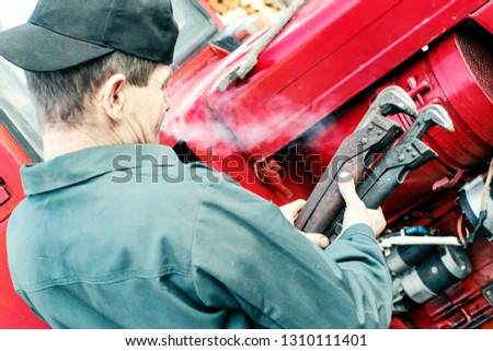 Farmer mechanic repairing red tractor. Male hand holding wrench, repairing tractor engine. #1310111401