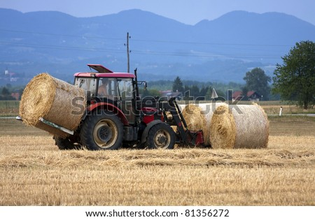 Farmer moving bales of hay with tractor.