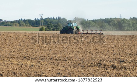 Farmer Ploughing Soil using Tractor with Mouldboard Plough on Sunny Day Сток-фото ©