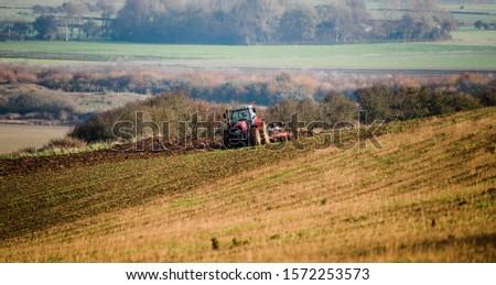 farmer plowing his fields in a beautiful autumnal landscape #1572253573
