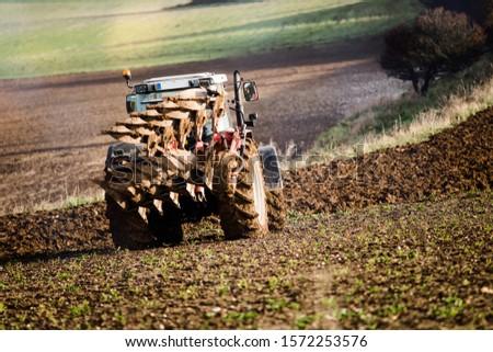 farmer plowing his fields in a beautiful autumnal landscape #1572253576
