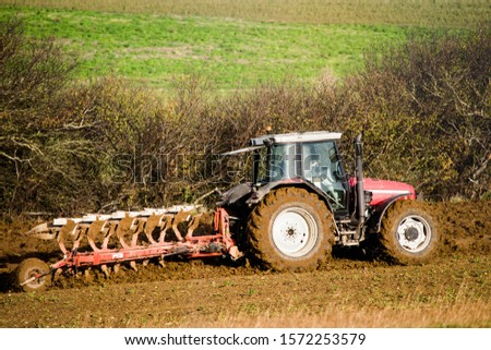 farmer plowing his fields in a beautiful autumnal landscape #1572253579