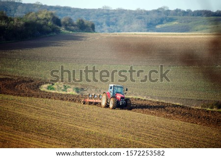 farmer plowing his fields in a beautiful autumnal landscape #1572253582