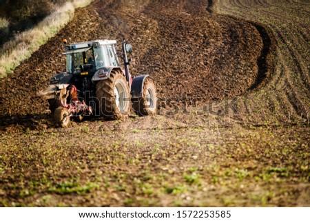 farmer plowing his fields in a beautiful autumnal landscape #1572253585